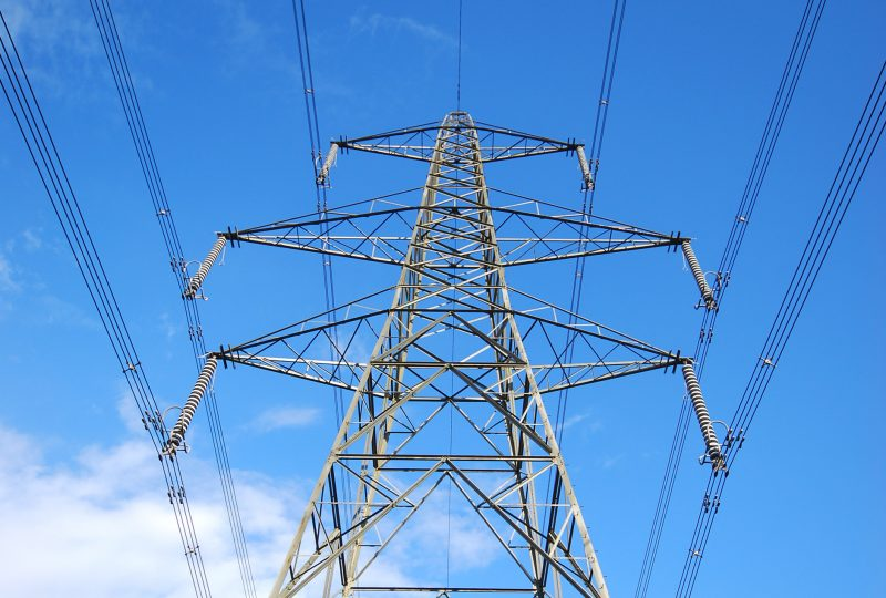 Wide angle view of electricity pylon against blue cloudy sky